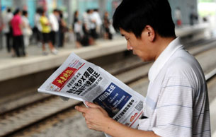 A man reads a newspaper report about a chemical plant whose protective dike was breached by waves in Dalian, Aug. 15, 2011.