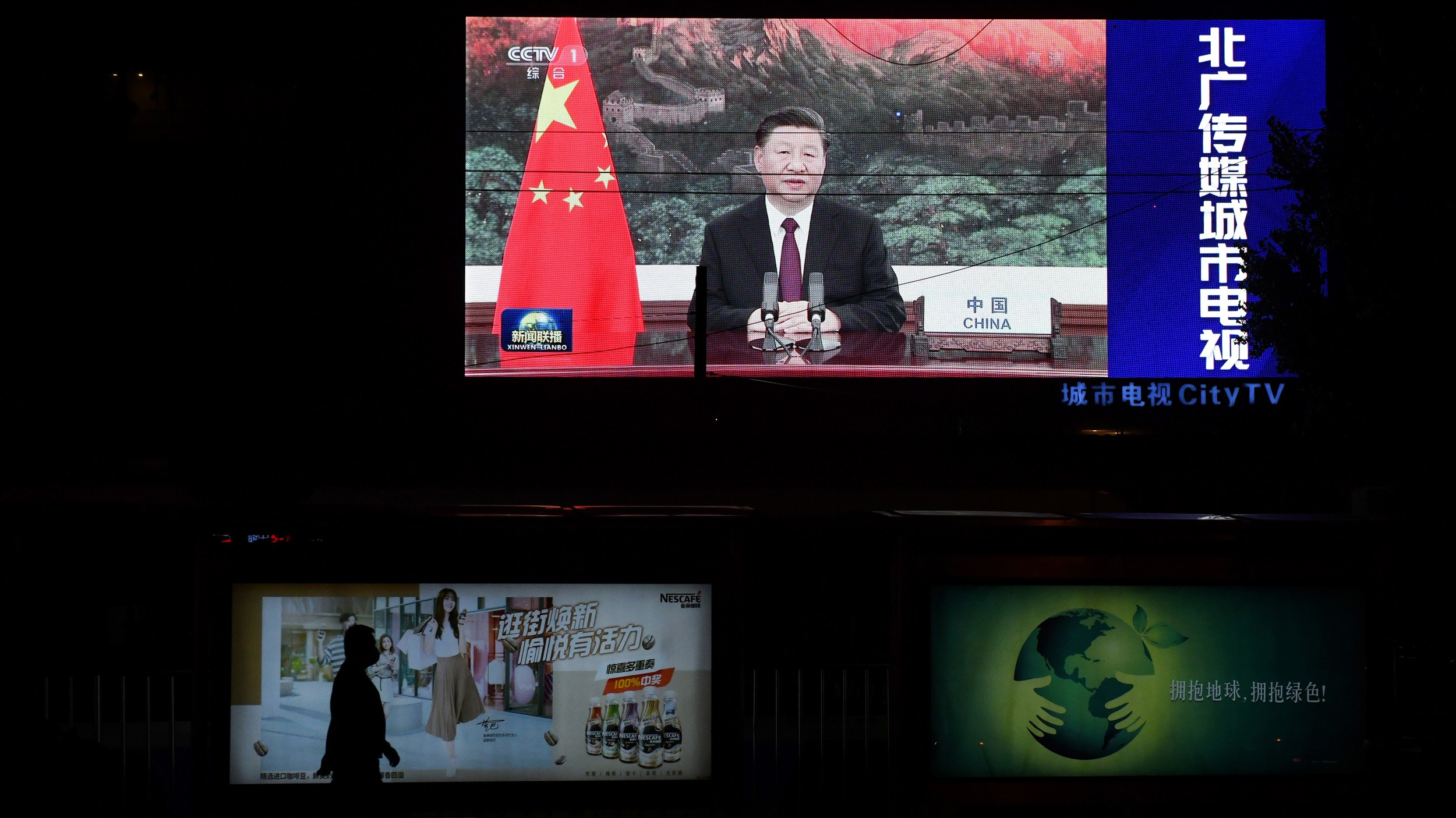 An image of Chinese President Xi Jinping appearing by video link at the United Nations 75th anniversary is seen on an outdoor screen as a pedestrian walks past below in Beijing, Sept. 22, 2020.