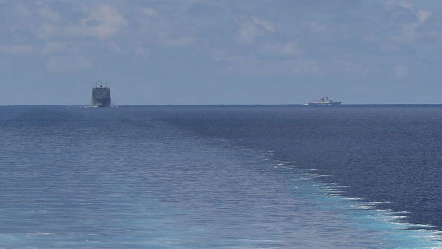 A photo taken from the littoral combat ship USS Montgomery, showing the USNS Cesar Chavez trailing it on the left, and a Chinese Navy warship on the right.