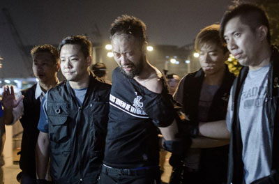 Ken Tsang is taken away by policemen before being allegedly beaten up by police forces outside the central government offices in Hong Kong, Oct. 15, 2014. Credit: AFP