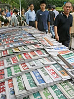 Sept. 14, 2006: Chinese shoppers walk past a kiosk selling domestic Chinese newspapers at People's Square in Shanghai. Photo: AFP/Mark Ralston