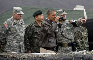 U.S. President Barack Obama looks through binoculars towards North Korea from the DMZ, March 25, 2012.