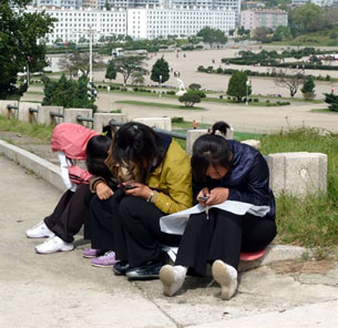 North Korean girls use mobile phones in a park in Pyongyang, Sept. 22, 2010.