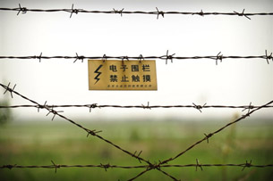 A warning sign is shown on a barbed-wire fence separating China and North Korea, May 27, 2009.
