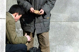 Two North Korean men make a blackmarket transaction, buying and selling U.S. dollars, outside a subway station in Pyongyang, Feb. 14, 2003. Credit: AFP