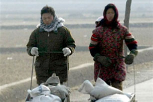 Two North Korean women push trolleys with their farm produce on the road to Pyongyang, Feb. 13, 2003. Credit: AFP
