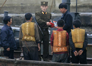 A North Korean border guard checks the documents of boat passengers in Sinuiju, Oct. 25, 2006.