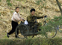 October 2006. A North Korean girl pushes a man in an improvised wheelchair opposite the Chinese border city of Dandong. Photo: AFP/Liu Jin