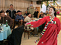 CHINA, Dandong: A North Korean waitress dances with a customer at a restaurant. Photo: AFP/Frederic J. Brown