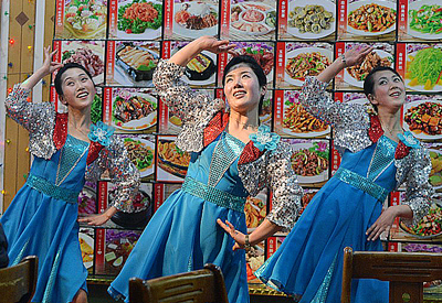 North Korean waitresses perform in front of a large menu at a North Korean restaurant in Dandong, northeastern China's Liaoning province, Feb. 11, 2013. Credit: AFP
