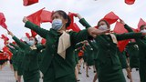 Women wearing face masks to help curb the spread of the coronavirus parade with flags during a rally to welcome the Eighth Congress of the Workers' Party of Korea at Kim Il Sung Square in Pyongyang, North Korea, Monday, Oct. 12, 2020.
