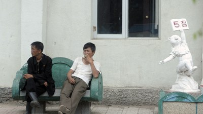 Two men rest outside an apartment building in the outskirts of Rason city in North Korea in this file photo.