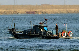 A North Korean patrol boat cruises the Yalu River between North Korea and China, Dec. 30, 2011.