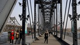 Visitors walk on the Broken Bridge over the Yalu river which separates North Korea's Sinuiju from China, in Dandong, Liaoning province, China March 19, 2021.