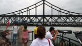 Chinese visitors look on from the Broken Bridge as a train travels on the Friendship Bridge across the Yalu river from North Korea to China, in Dandong, Liaoning province, China June 10, 2018. Picture taken June 10, 2018.