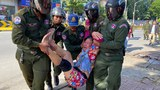 A Cambodian woman is taken away by police after peacefully protesting outside the Chinese embassy in Phnom Penh, Oct. 23, 2020.