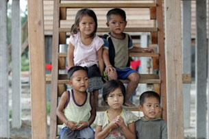 Children sit on the stairs of a house at the Sop On resettlement village in Laos' Nakai plateau, June 28, 2007.