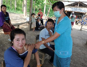 A woman receives a shot at a village in northern Laos's Luang Prabang province, May 4, 2012.