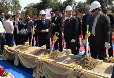 Officials use shovels to ceremoniously break ground on the Savannakhet-Lao Bao railway project, Dec. 18, 2013.