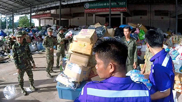 Soldiers and volunteer aid workers staff a warehouse of supplies for Lao villagers displaced by flooding in Paksong district, southwestern Laos' Champassak province, July 28, 2018.