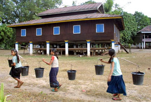 Three young Laotian girls carry water in a village in Khammouane province, Nov. 27, 2002.
