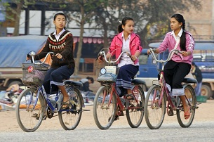 Girls ride their bikes to school in Luang Prabang, Oct. 10, 2010.