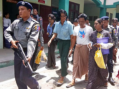 Antiwar activist Aung Hmine San is escorted to court by an armed guard to face charges for violating Article 19 of Myanmar's Peaceful Assembly and Procession Law in central Myanmar's Mandalay, May 9, 2018.