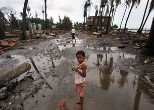 A boy stands amid destroyed buildings in the Rakhine capital of Sittwe, June 16, 2012.