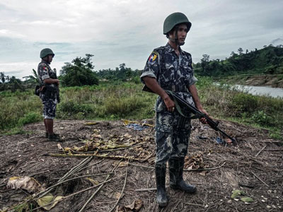 Myanmar border police stand guard in Tinmay village, Buthidaung township, in the northern part of western Myanmar's Rakhine state, July 14, 2017.