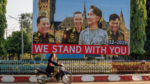 A motorcyclist rides past a billboard depicting Myanmar State Counselor Aung San Su Kyi with the three military ministers against the backdrop of the UN's International Court of Justice, displayed along a road in Hpa-an, southeastern Myanmar's Kayin state, Nov. 28, 2019.