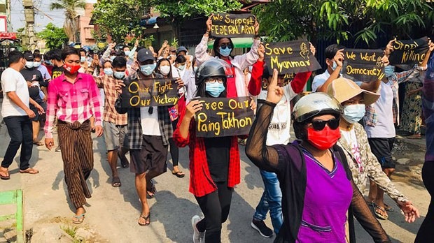 Myanmar anti-junta protesters march through a neighborhood in the central Myanmar city of Mandalay, April 12, 2021.