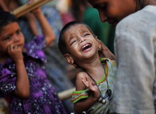 A Rohingya mother comforts her child as they wait for medical care at a camp on the outskirts of Sittwe, Nov. 2, 2012.