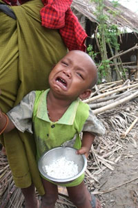 BURMA, Dedaye : A survivor of Cyclone Nargis clutches a bowl of rice in the town of Dedaye in the Irrawaddy delta on June 9, 2008. Photo: AFP