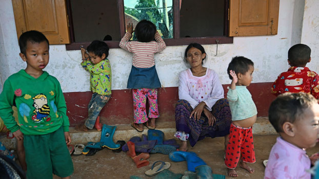 A woman and children affected by clashes between the Myanmar military and ethnic rebel groups seek temporary shelter at Kho Lone Buddhist monastery in Kutkai, Myanmar's northern Shan State, Aug. 25, 2019.