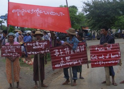 Demonstrators carry signs protesting the mine in Salingyi township, Sept. 5, 2012.
