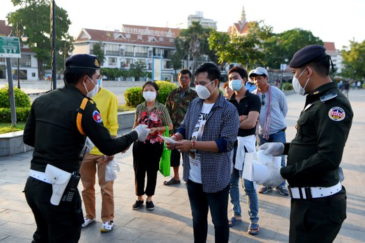 Military police officers hand out free facemasks to people amid concerns over the coronavirus at a park in Phnom Penh, Nov. 12, 2020.