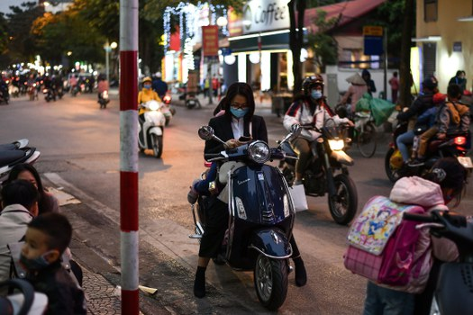 A woman wearing a facemask checks her smartphone while waiting on her scooter along a street in Hanoi, Dec. 1, 2020.