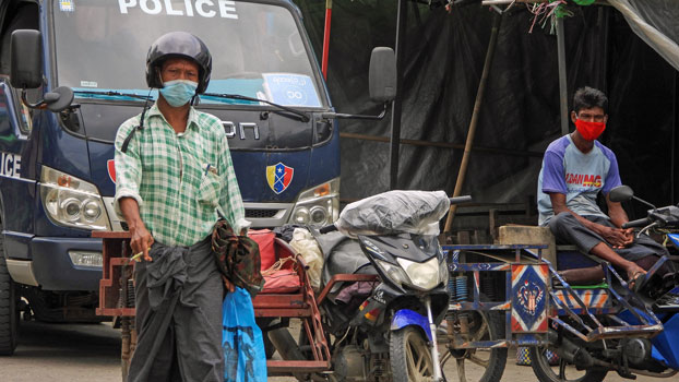 A police officer observes people wearing face masks on a street during a lockdown amid the coronavirus pandemic in Sittwe, capital of western Myanmar's Rakhine state, Aug. 23, 2020.