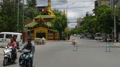 Motorists ride past makeshift barriers erected by the military along a road in Mandalay, June 23, 2021.