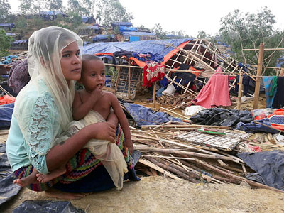 Rohingya refugees sit near a house destroyed by Cyclone Mora in a camp in Cox's Bazar, Bangladesh, May 31, 2017.