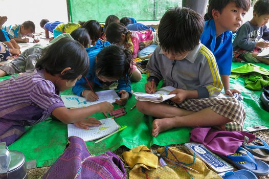 Children displaced by fighting between the military and members of the People's Defense Force attend a school lesson under a makeshift structure as they take refuge in the jungle near Demoso, Kayah state, July 3, 2021. AFP