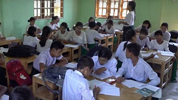 Myanmar students complete a writing assignment at a school in Sittwe, western Myanmar's Rakhine state, in 2019.