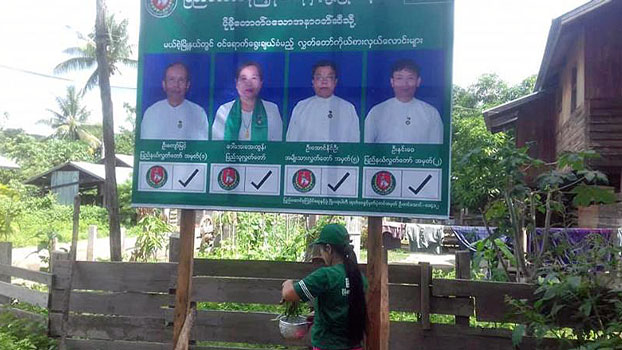 Hnin Wai (R), a USDP candidate disqualified by Myanmar election authorities over citizenship requirements, is shown on a party billboard in eastern Myanmar's Kayah state, October 2020.