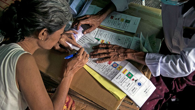 A senior citizen completes an election ballot inside her home during advance voting in Myanmar's commercial hub Yangon, Oct. 29, 2020.