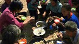 Ethnic Kokang refugees eat a meal of beans and pickled vegetables in the open air. Feb. 27, 2015