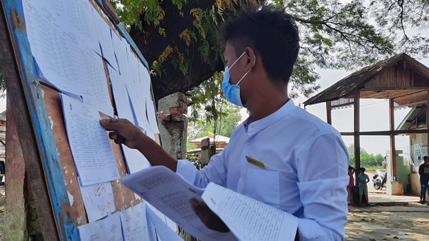 A local election official checks a voter list on a board at a polling station in Dawei township, southern Myanmar's Tanintharyi region, Nov. 8, 2020.