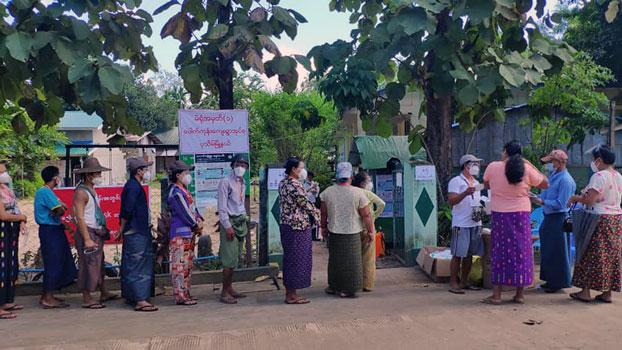 Myanmar voters wait in line outside a village polling station in Pathein township, Ayeyarwady region, Nov. 8, 2020.