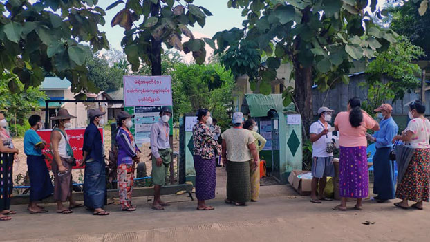 Myanmar voters wait in line outside a village polling station in Pathein township, Ayeyarwady region, Nov. 8, 2020.