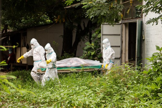 This photo taken and received courtesy of an anonymous source via Facebook on July 6, 2021 shows volunteers wearing personal protective equipment (PPE) carrying a body of a Covid-19 coronavirus victim for burial at Myoma Cemetery in Yangon, amid a surge in cases in the country. HANDOUT / FACEBOOK / AFP
