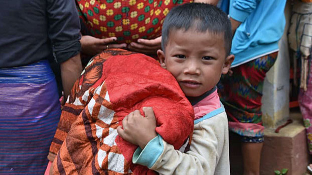 A young boy carries a blanket while fleeing to the town of Kutkai amid fighting between Myanmar forces and rebel ethnic armies in northern Shan state, Sept. 2, 2019.